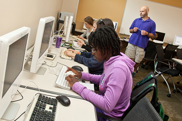 syudents working in computer lab with teacher looking on